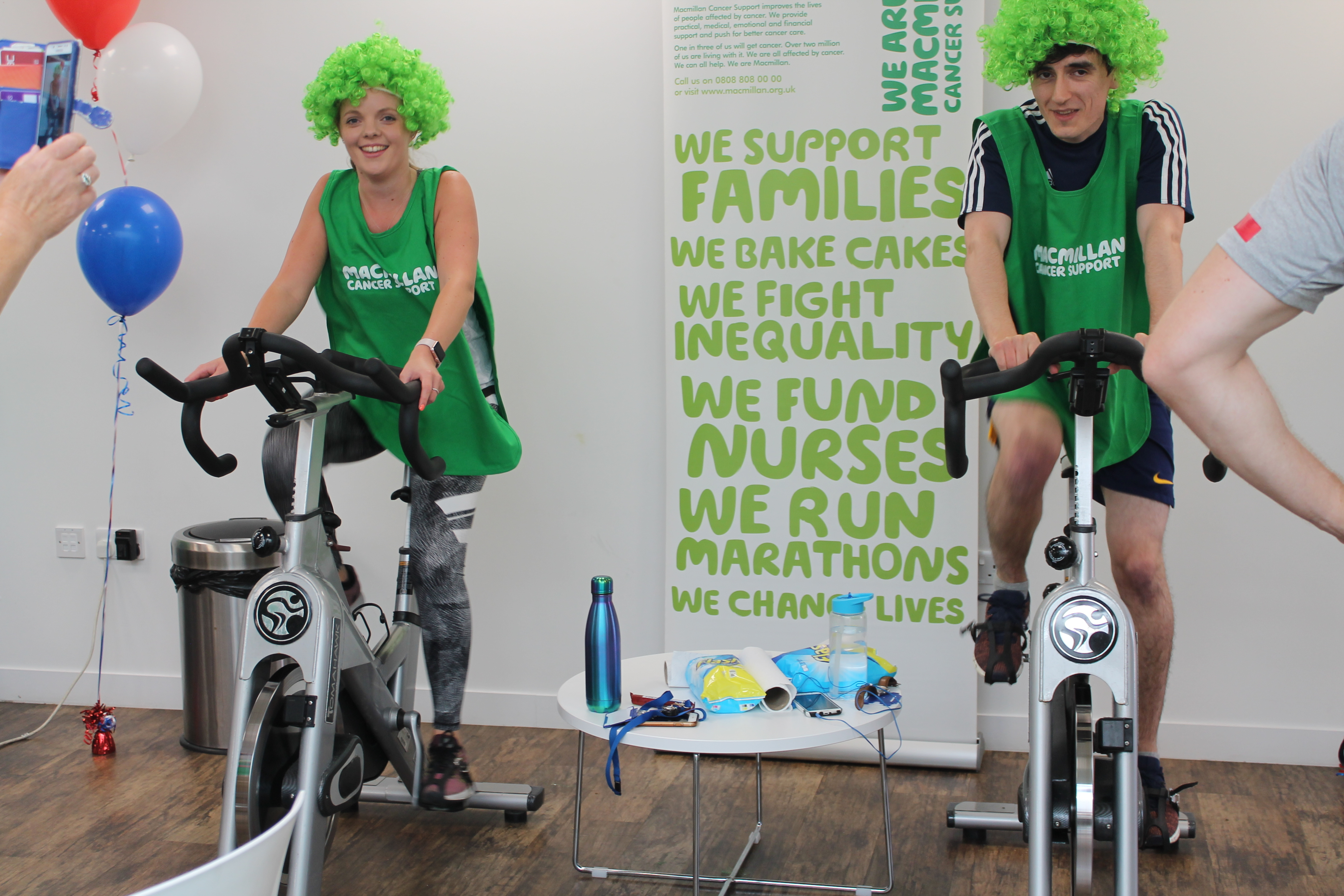 CliniMed staff riding on the training bikes whilst wearing green wigs